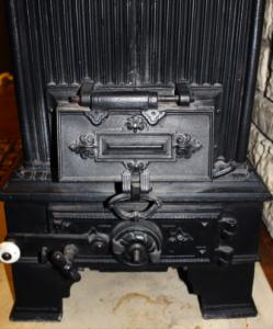 Gammel brændeovn i jern uden glas
